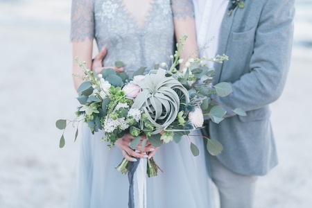 Newly married couple holding wedding bouquet.