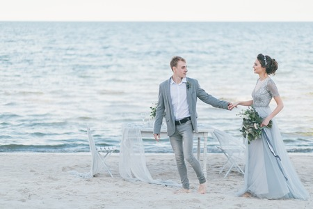 Delighted newly married couple holding hands by the sea. Standard-Bild