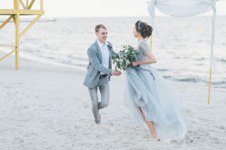 Happy newly-weds are having fun and running by the sea.