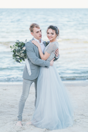 Groom holding in arms bride by the sea. Standard-Bild