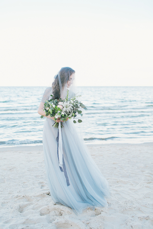 Tender bride in veil with wedding bouquet  by the sea. Standard-Bild