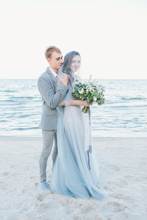 Groom holding bride in veil by the sea.