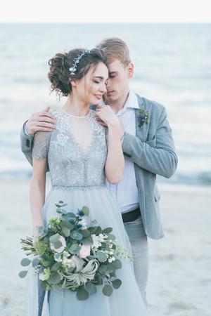 Newly-weds cuddling at the seashore. Stock Photo