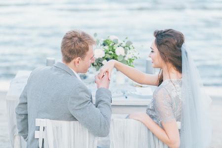 Bräutigam wünschte der Hand der Braut an der Küste zu küssen. Standard-Bild