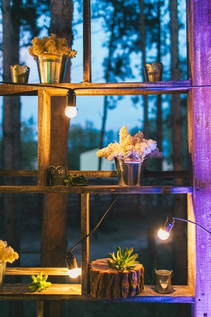 Rustic wedding decor, shelf stand with lilac arrangements and succulents.