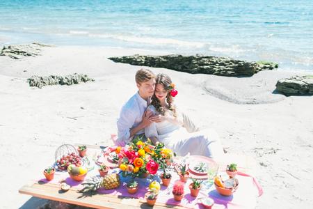 Newly married couple having breakfast at the seashore.