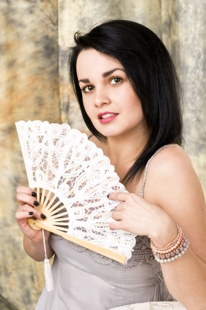 A beautiful woman with a fan . Portrait of an attractive young brunette . photo