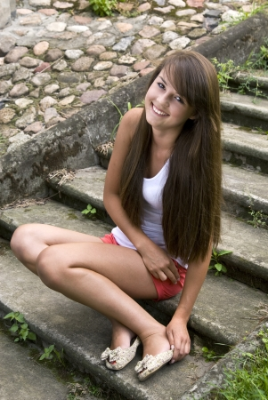 sexy girl sitting: Pretty happy young brunette posing outdoors .