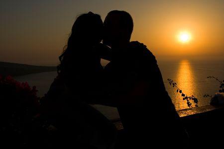 couple lit: Silueta de una pareja bes�ndose en la puesta de sol
