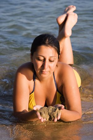 Beautifull Woman laying by the shore of the Aegean Sea with a golden tan Stock Photo - 2831291