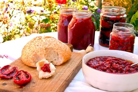 Composition of roasted tomatoes with herbs, jars of canned tomatoes and peppers and bread brushed with tomato-pepper mixture. Stock Photo