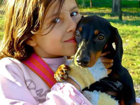 bulgaria girl: Stara Zagora, Bulgaria - October 23, 2010, Happy girl enjoys his dachshund dog and kissed him in the park. Editorial