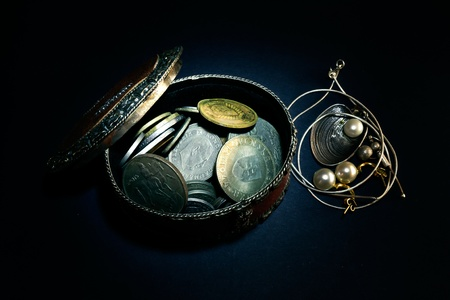 Various old coins from around the world in a brown box on a black background Stock Photo