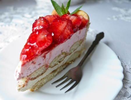 Homemade cake parfait slice with fresh sliced strawberries on white plate