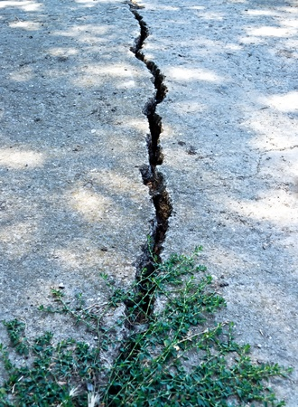 A deep crack in the concrete pavement of the road Stock Photo