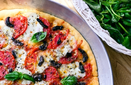 Pizza with mozzarella, tomatoes, mushrooms and basil photo