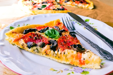 Piece of Pizza with mozzarella, tomatoes, mushrooms and basil in a white bowl