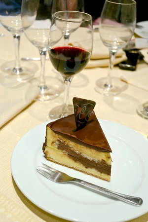 A piece of chocolate cake in a white bowl and a glass of red wine back Stock Photo - 11375733