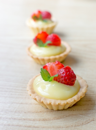 Sweet tartelettes filled with vanilla cream and strawberries photo