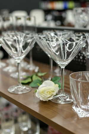 Empty cocktail glasses and a white rose