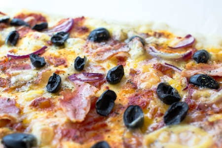 Pizza arranged with ham, olives, onions and tomato sauce after baking