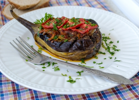 Aubergine stuffed with vegetables in white plate Stock Photo