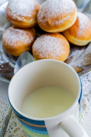 Donuts with cream, sprinkled with powdered sugar and cup buttermilk