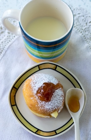 Donuts with cream, sprinkled with powdered sugar and cup buttermilk photo