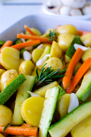 Fresh potatoes on a baking with vegetables Stock Photo