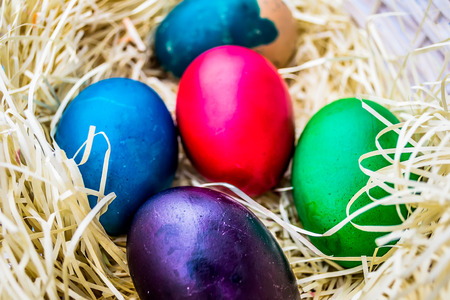 Several painted Easter eggs laid in straw nest