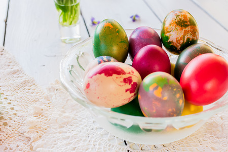 Colorful Easter eggs on white wooden table