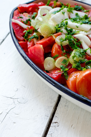 Tomato salad with onion and parsley in a metal tray