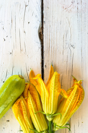 courgettes: Edible flowers of courgettes and courgettes on a white table Stock Photo
