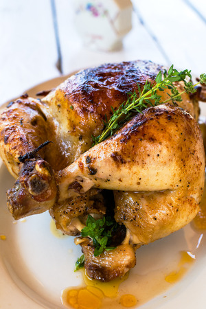 Whole roast chicken in a white plate on a white wooden table Stock Photo