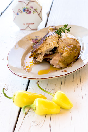 Piece of roast chicken in a white plate on a white wooden table