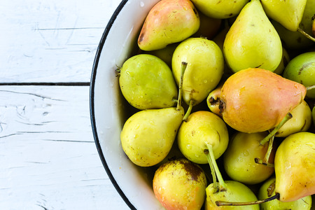 Pile of fresh and ripe pears in a metal bowl on white wooden table