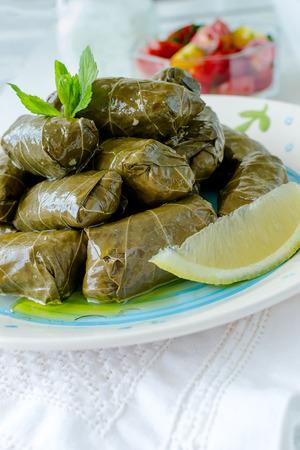 hojas vid: Tradicional búlgara vid rellenas casera deja con arroz y adornado con los tomates frescos, limón y salsa de yogur y eneldo