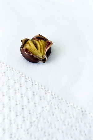 consist: Edible chestnut consist of split coat on a white tablecloth