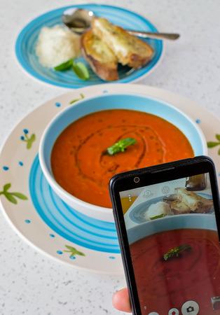 Fresh tomato soup - look through smart phone Stock Photo