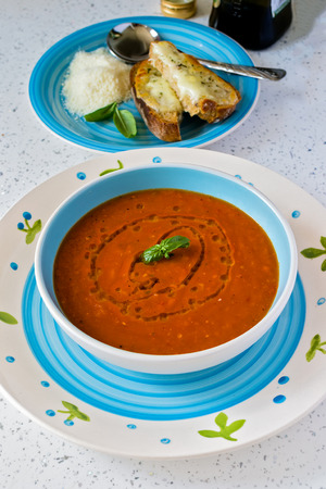 Fresh tomato soup in blue and white bowl with basil