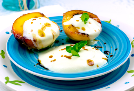 Grilled peaches garnished with mascarpone cream and sour cream