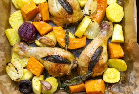 Roasted chicken legs with vegetables, herbs and pumpkin Stock Photo