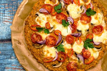 Pizza au plat de patate douce et graines d'avoine, garnie de champignons, oignons, mozzarella et tomates cerises Banque d'images