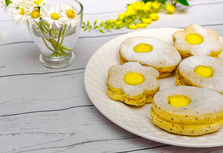 Easter biscuits like eggs with citrus cream on white wooden table
