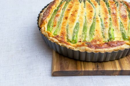 Tart with green asparagus and toasted cheese on the table Stockfoto