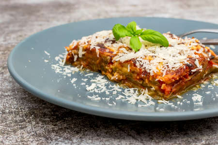 Parmigiana di Melanzane - strips of fried eggplant with parmesan, baked in tomato sauce in a ceramic pan Stock fotó