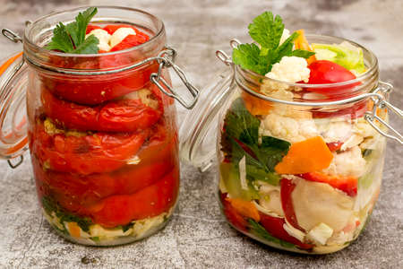 Jar of pickled cauliflower, red bell peppers, carrots and green tomatoes Standard-Bild