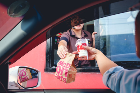 Bangkok, Thailand - Mar 4, 2017: Unidentified customer receiving hamburger and ice cream after order and buy it from McDonald's drive thru service, McDonald's is an American fast food restaurant chain Editoriali