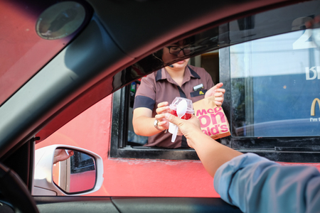 Bangkok, Thailand - Mar 4, 2017: Unidentified customer receiving hamburger and ice cream after order and buy it from McDonald's drive thru service, McDonald's is an American fast food restaurant chain Редакционное