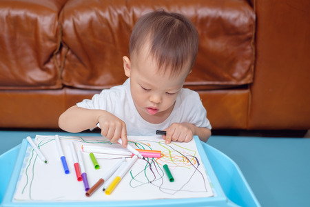 Cute little Asian 18 months / 1 year old toddler boy child drawing, scribbling with colorful maker, kid write in living room at home,Creative play for toddlers, fine motor skills development concept